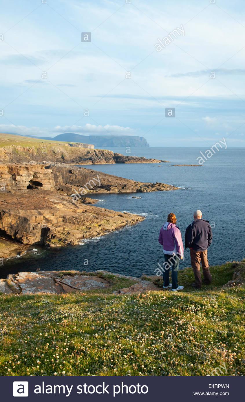 A couple walking along the coastline near Yesnaby, Mainland, with the cliffs of Hoy visible in the distance, Orkney, - Stock Image
