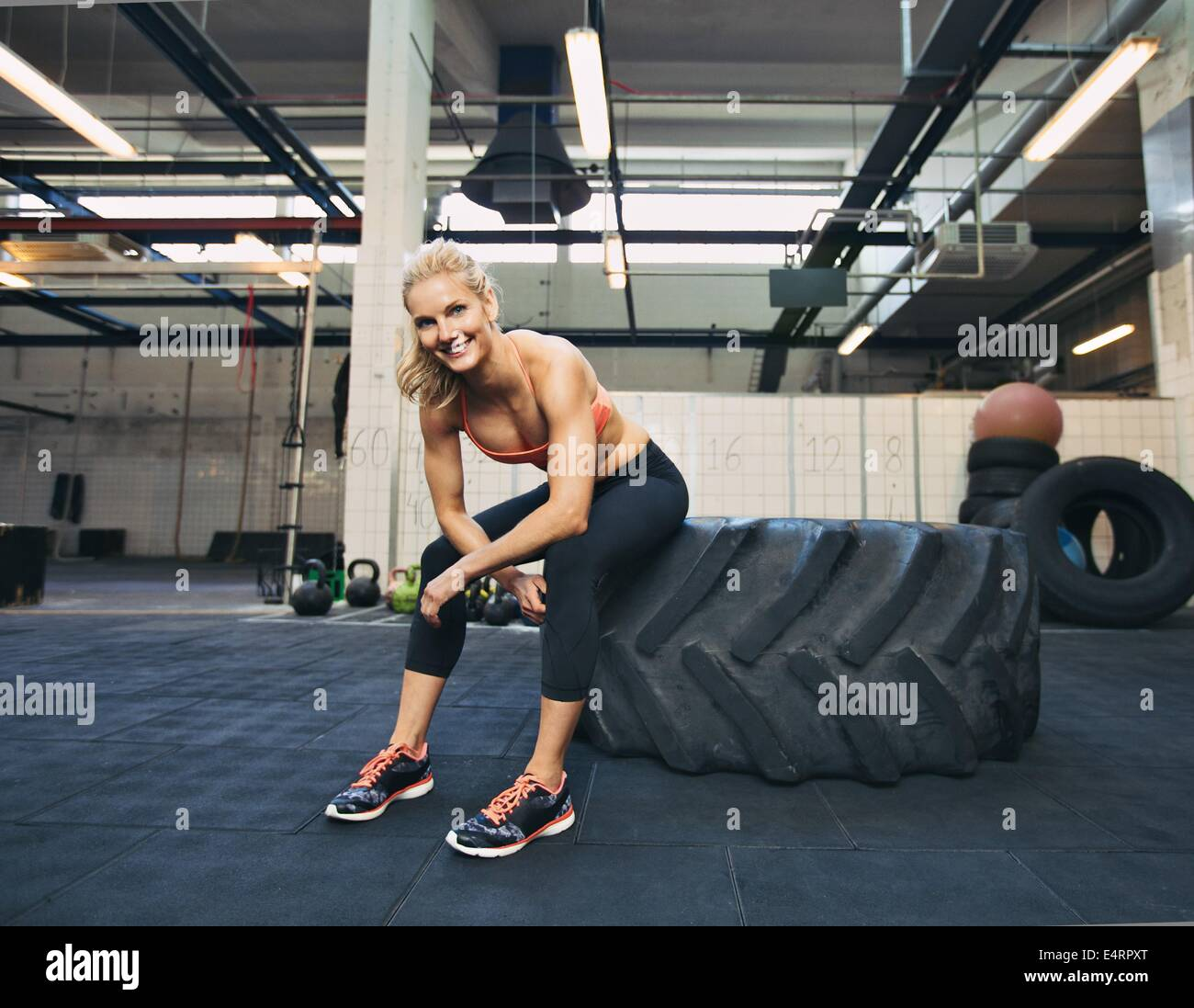 Woman sitting on tire and smiling at camera at gym. Crossfit female athlete taking rest after working out. Stock Photo