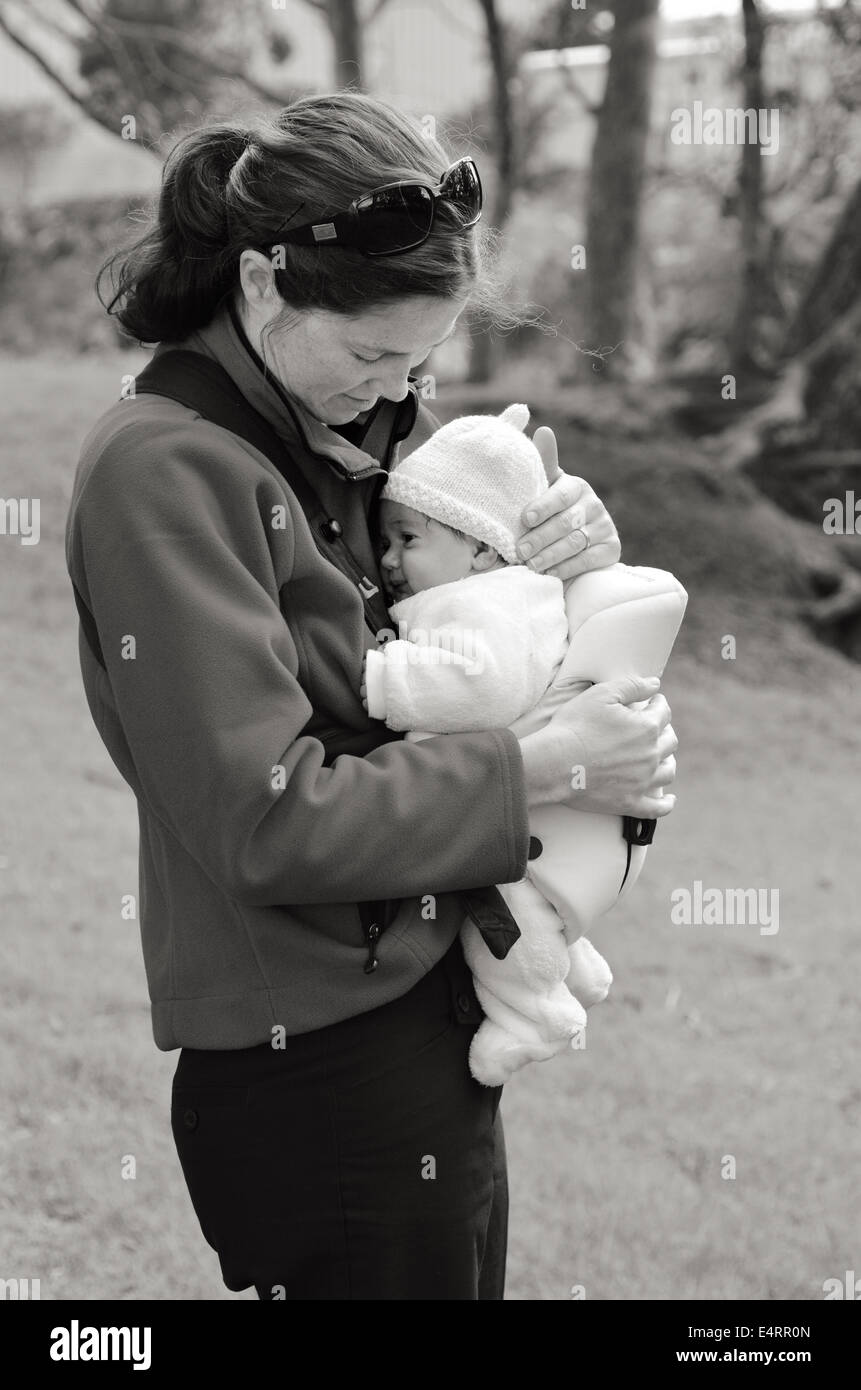 Mother carry newborn baby on baby carrier. concept photo of motherhood, baby, newborn. (BW) - Stock Image