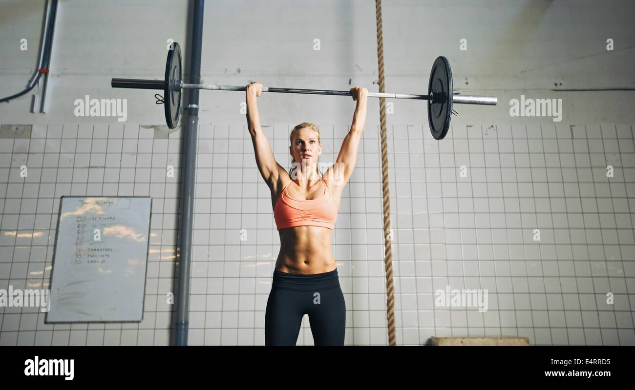 Muscular young female athlete doing weightlifting at crossfit gym. Fit young woman model lifting heavy weights at - Stock Image