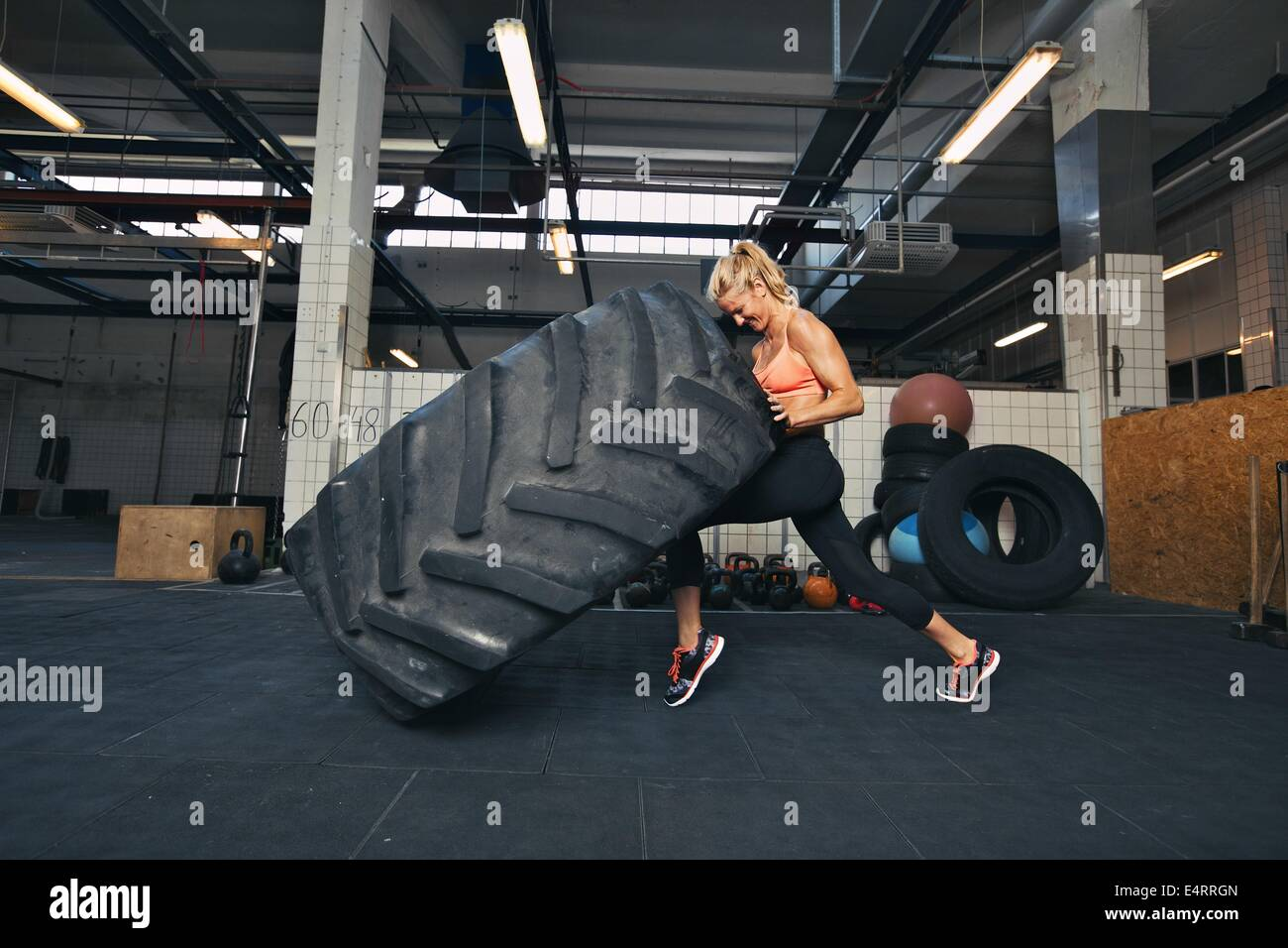 Fit female athlete working out with a huge tire, turning and flipping in the gym. Crossfit woman exercising with - Stock Image
