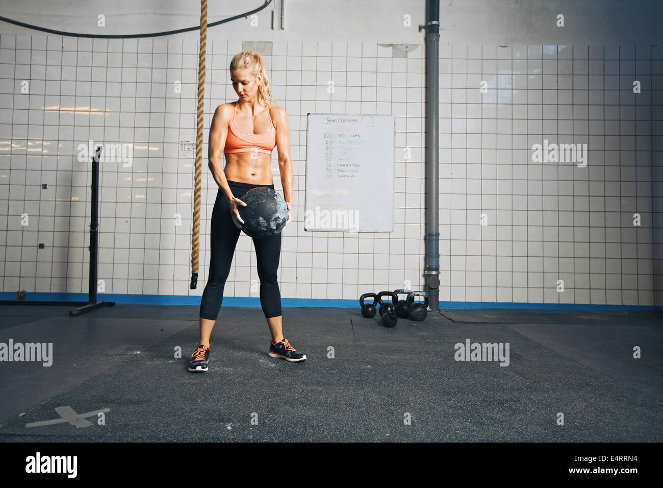 Fitness woman working out with a medicine ball. Strong young caucasian woman doing crossfit workout at gym. - Stock Image
