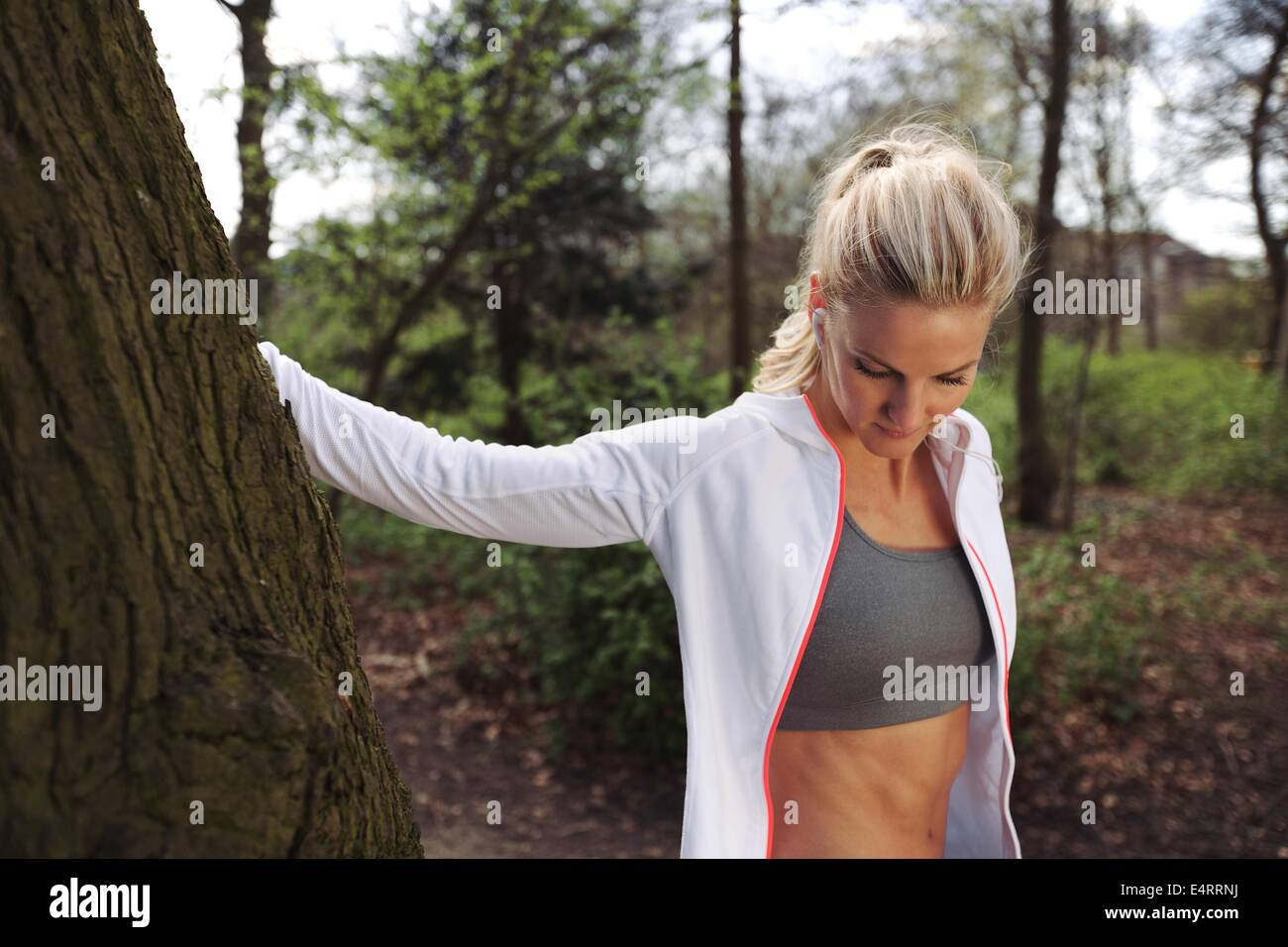 Beautiful young woman resting by a tree after jogging in a park. Fit female athlete taking a break after running. - Stock Image
