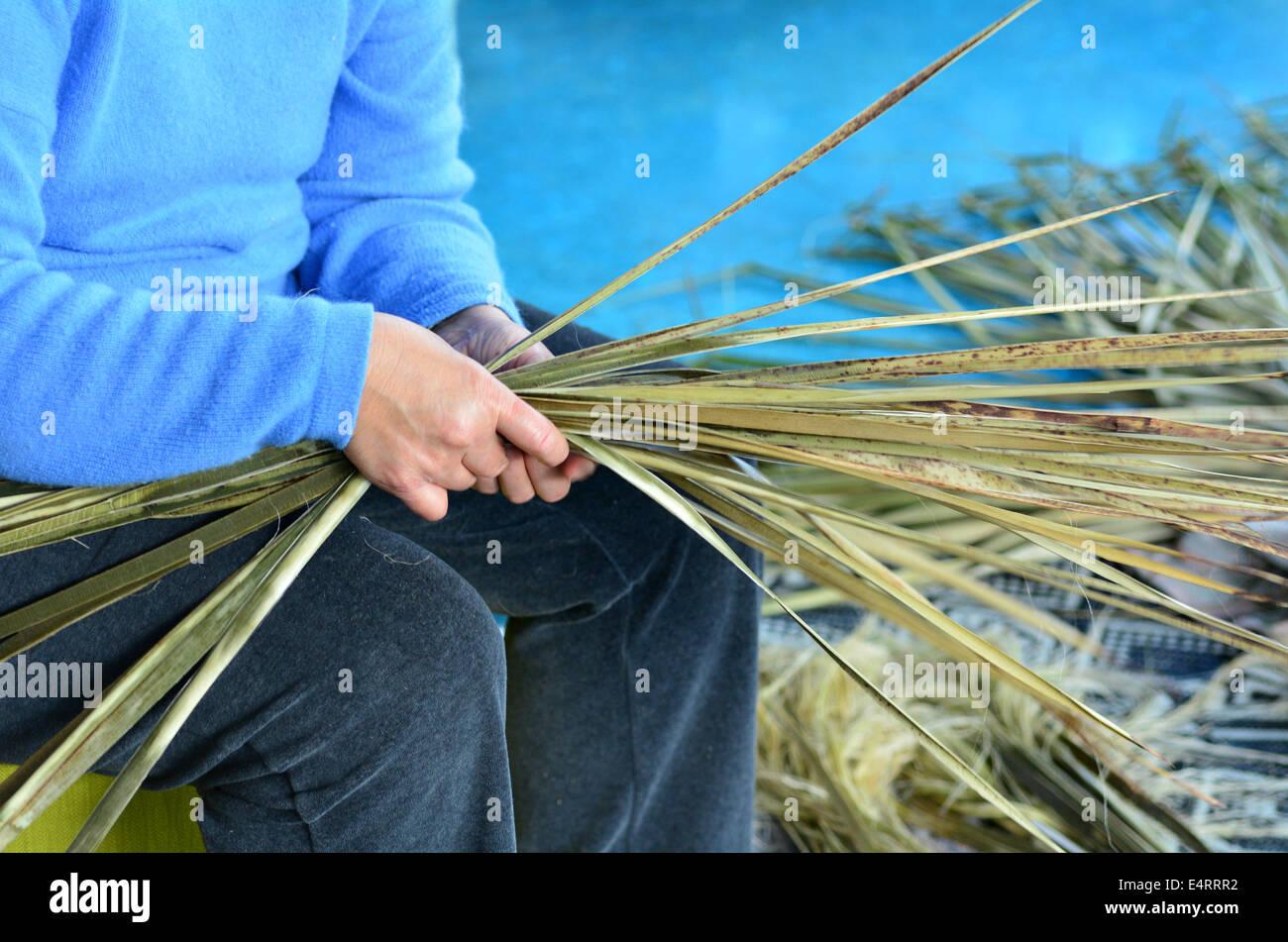 An old Maori woman weaving a traditional Maori woven artwork. - Stock Image