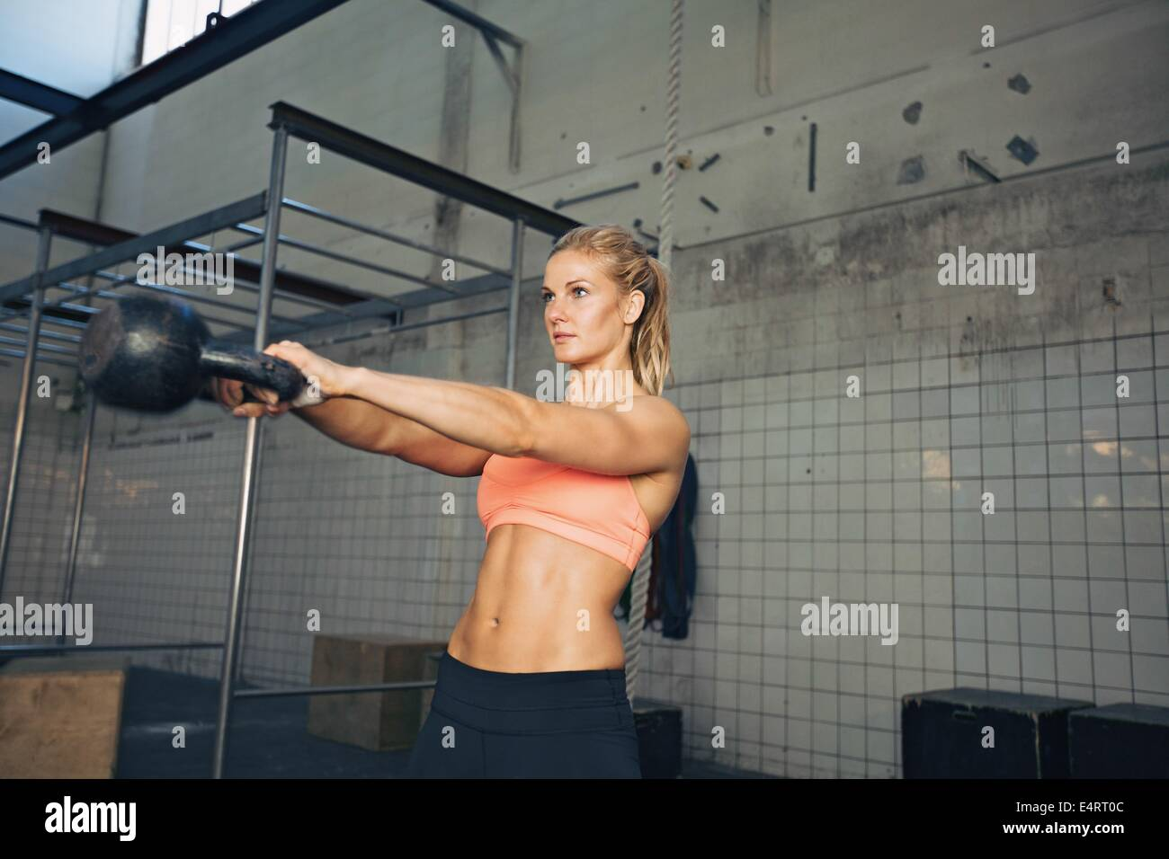 Fitness woman swinging kettle bell at gym. Young caucasian woman doing swing exercise with a kettlebell as a routine - Stock Image