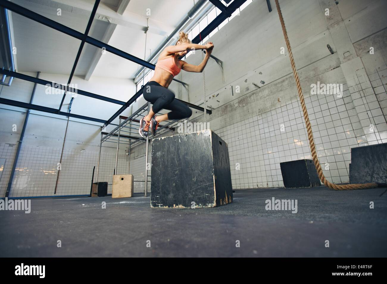 Low angle view of young female athlete box jumping at a crossfit gym. Fit woman is performing box jumps at gym. - Stock Image
