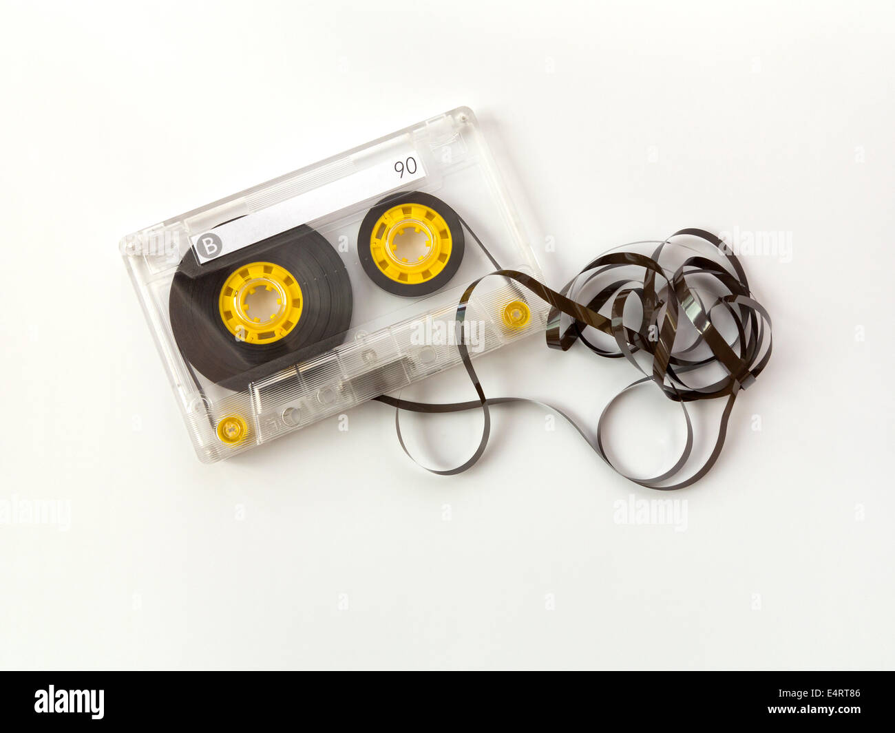 A single un-branded audio compact cassette with blank label and a small amount of tangled tape out of the case - Stock Image