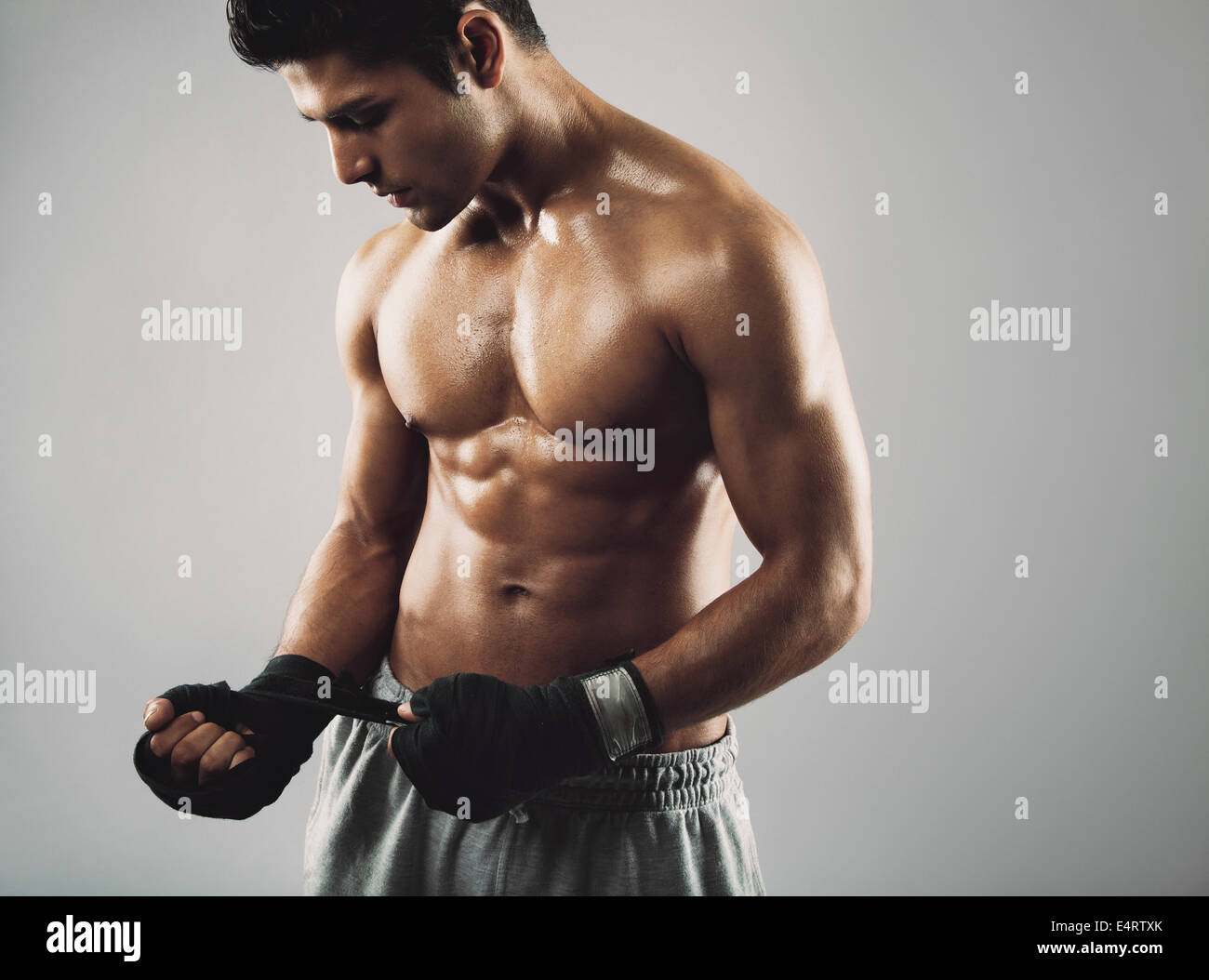 Young male boxer wrapping his hands in boxing tape before a fight. Hispanic young male fitness model. - Stock Image