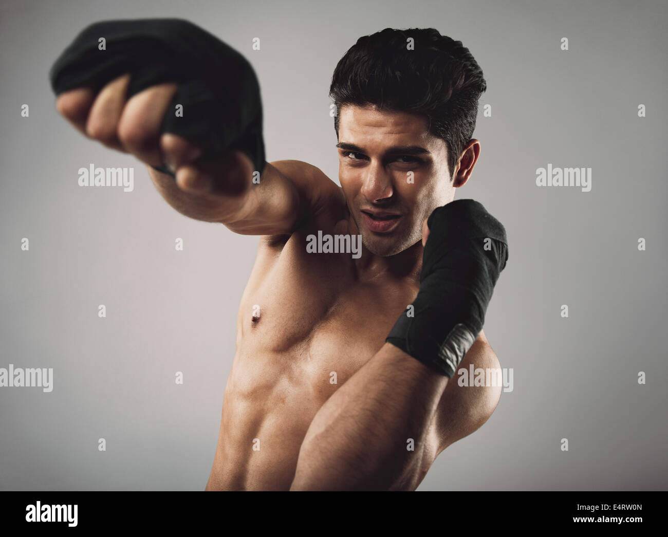 Hispanic young man practicing shadow boxing. Shirtless masculine male model with boxing gloves on grey background. - Stock Image