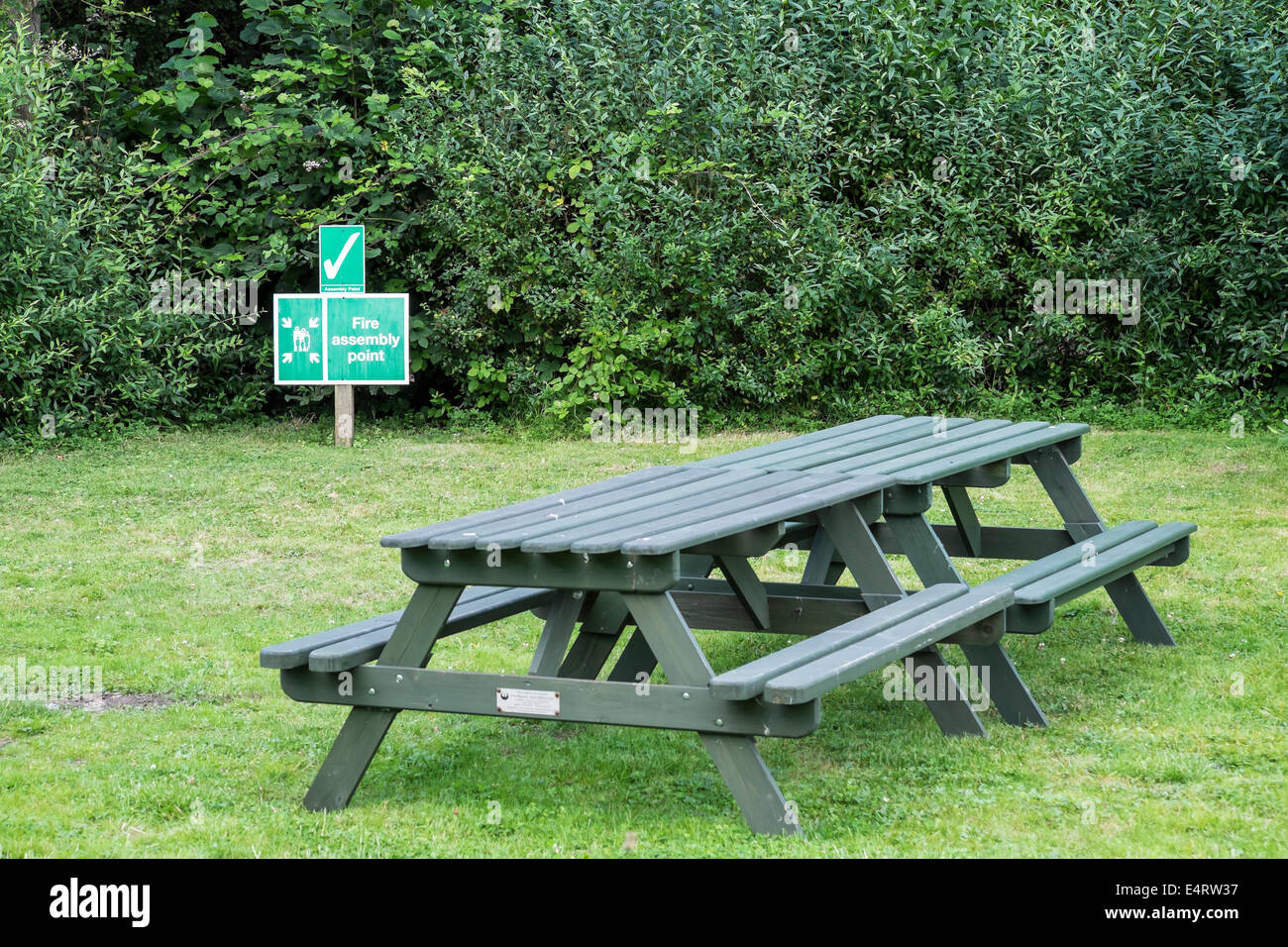 Picnic bench and fire assembly point sign - Stock Image
