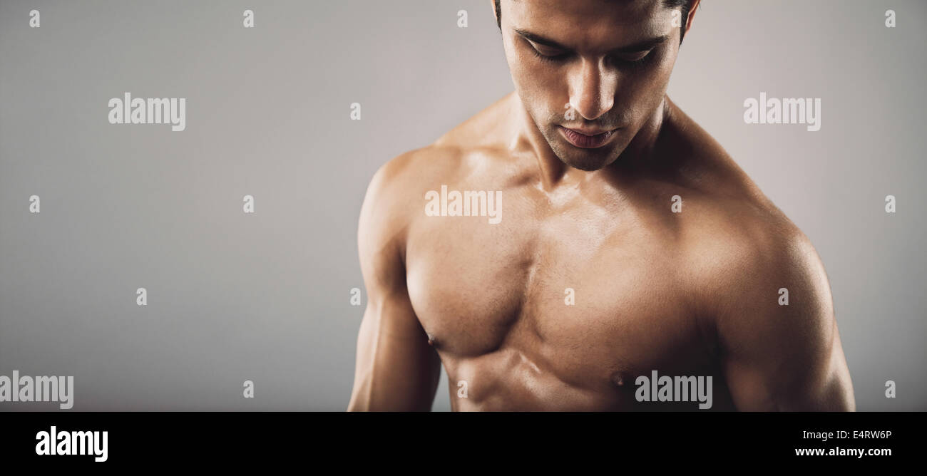 Portrait of fit masculine shirtless man  looking down. Wide panoramic crop with copy space. Workout and fitness - Stock Image