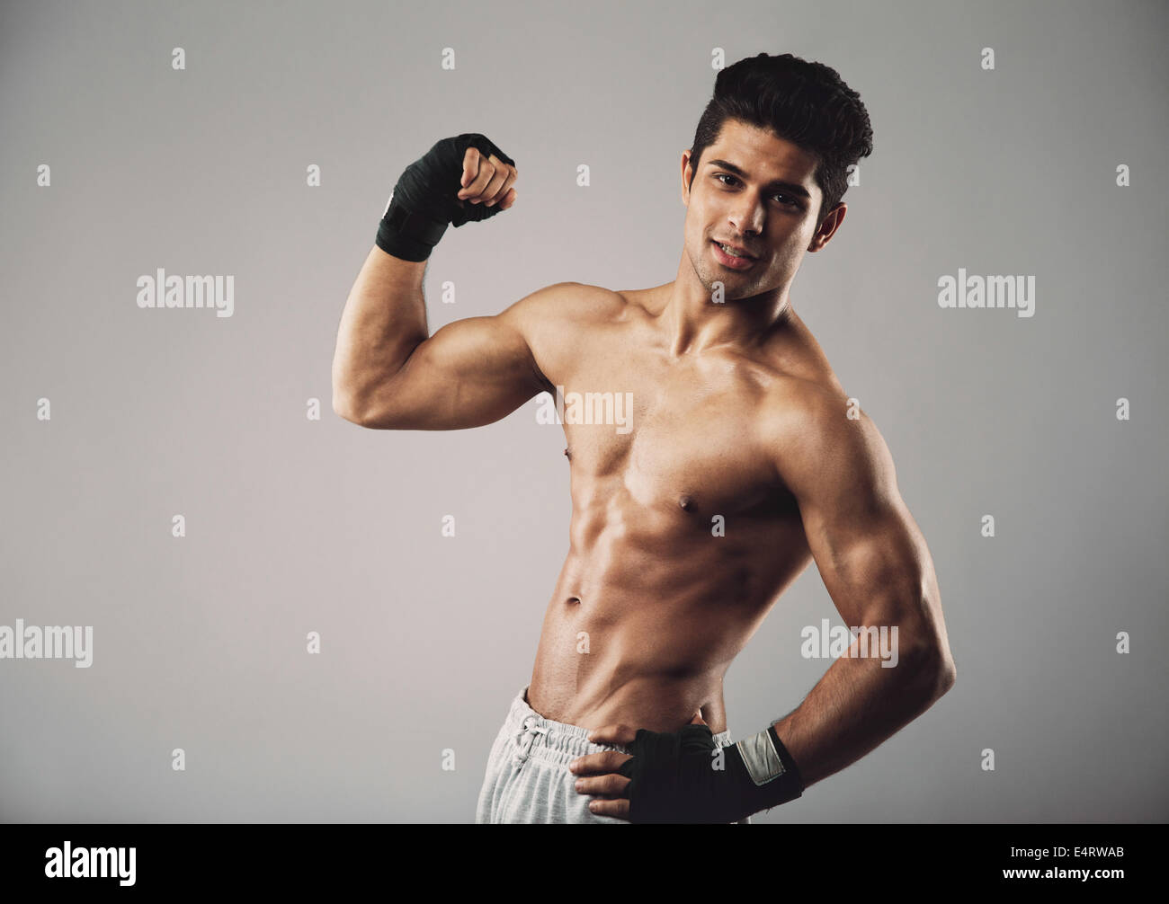 Portrait of muscular man pulling his bicep to show off. Hispanic young muscular man flexing his biceps on grey background. - Stock Image