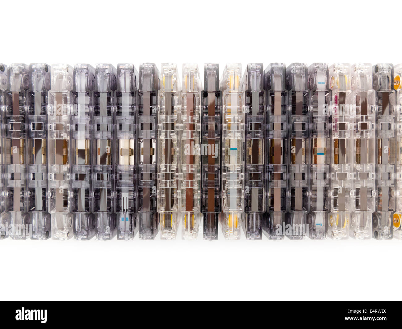 A stacked row of mixed compact  audio cassettes edge on, some showing tape, others tape leader, all in a variety - Stock Image