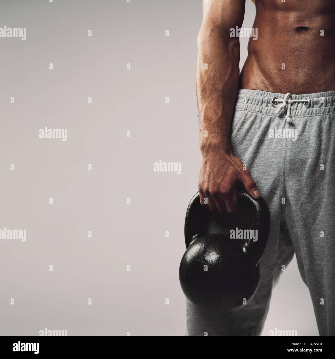 Close up image of young man's hand holding kettlebell. Crossfit workout concept with copyspace on grey background. - Stock Image
