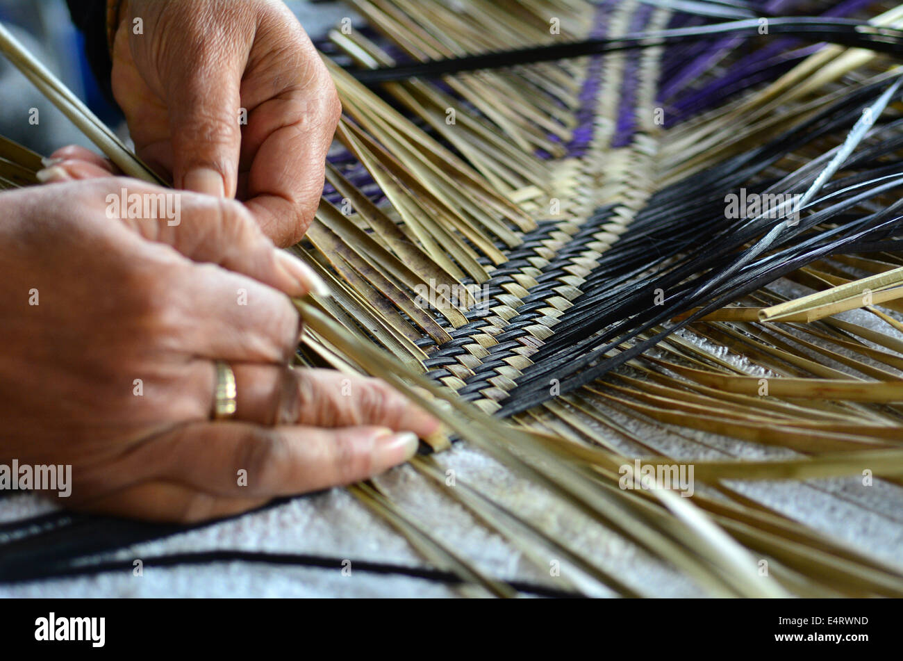 Hands of an old Maori woman weaving a traditional Maori woven artwork. - Stock Image