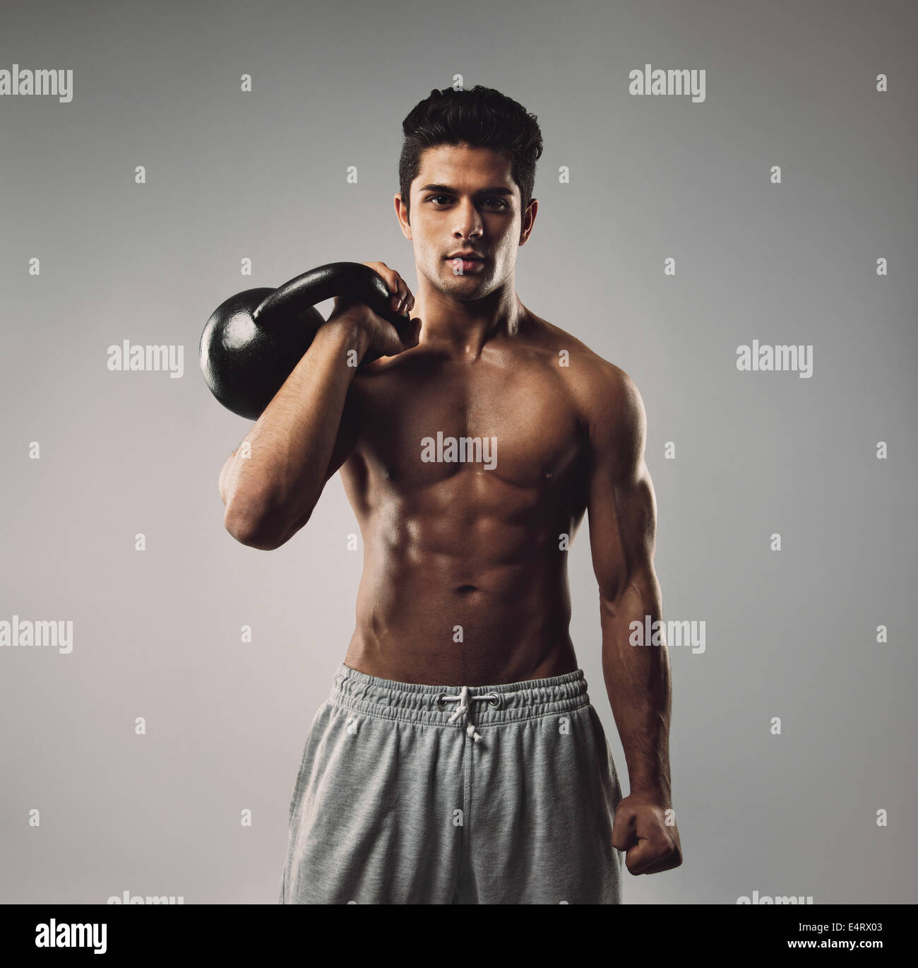 Portrait of strong young man working out with kettle bell. Young muscular guy with crossfit equipment on grey background. - Stock Image