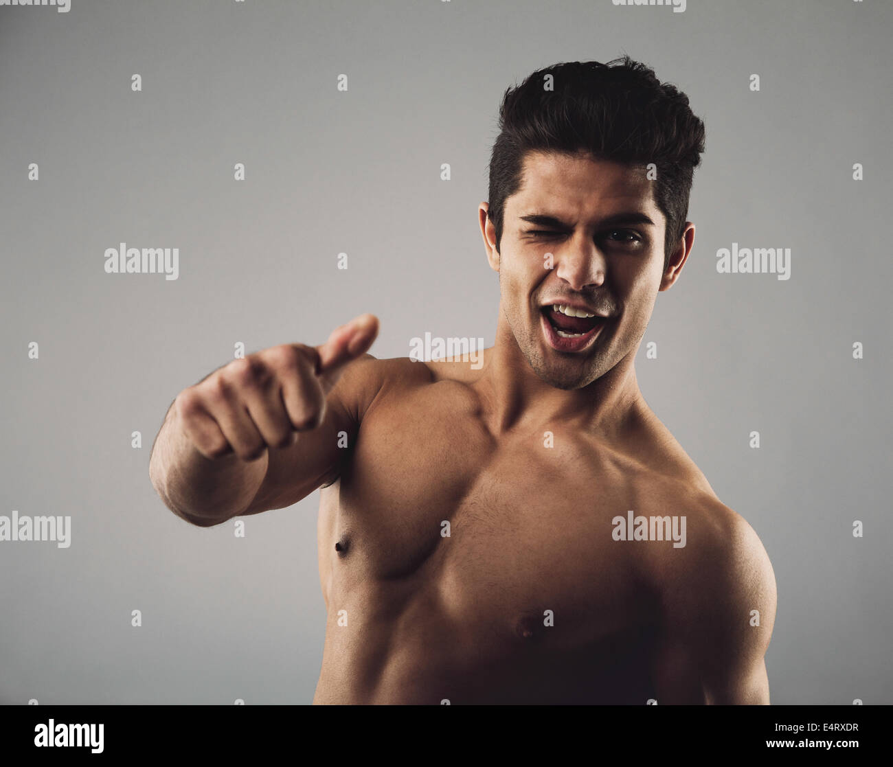 Portrait of a happy young man with muscular physique winking and giving a thumbs up sign. Shirtless young hispanic - Stock Image