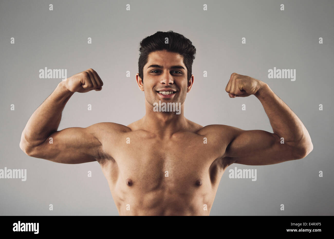 Portrait of hispanic young muscular man flexing his biceps isolated on grey background. Happy masculine man pulling - Stock Image