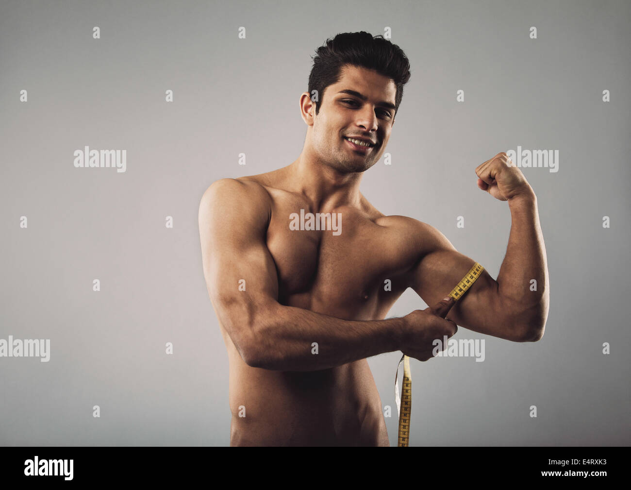 Portrait of young man measuring his biceps with a tape measure. Shirtless male model with muscular physique on grey - Stock Image
