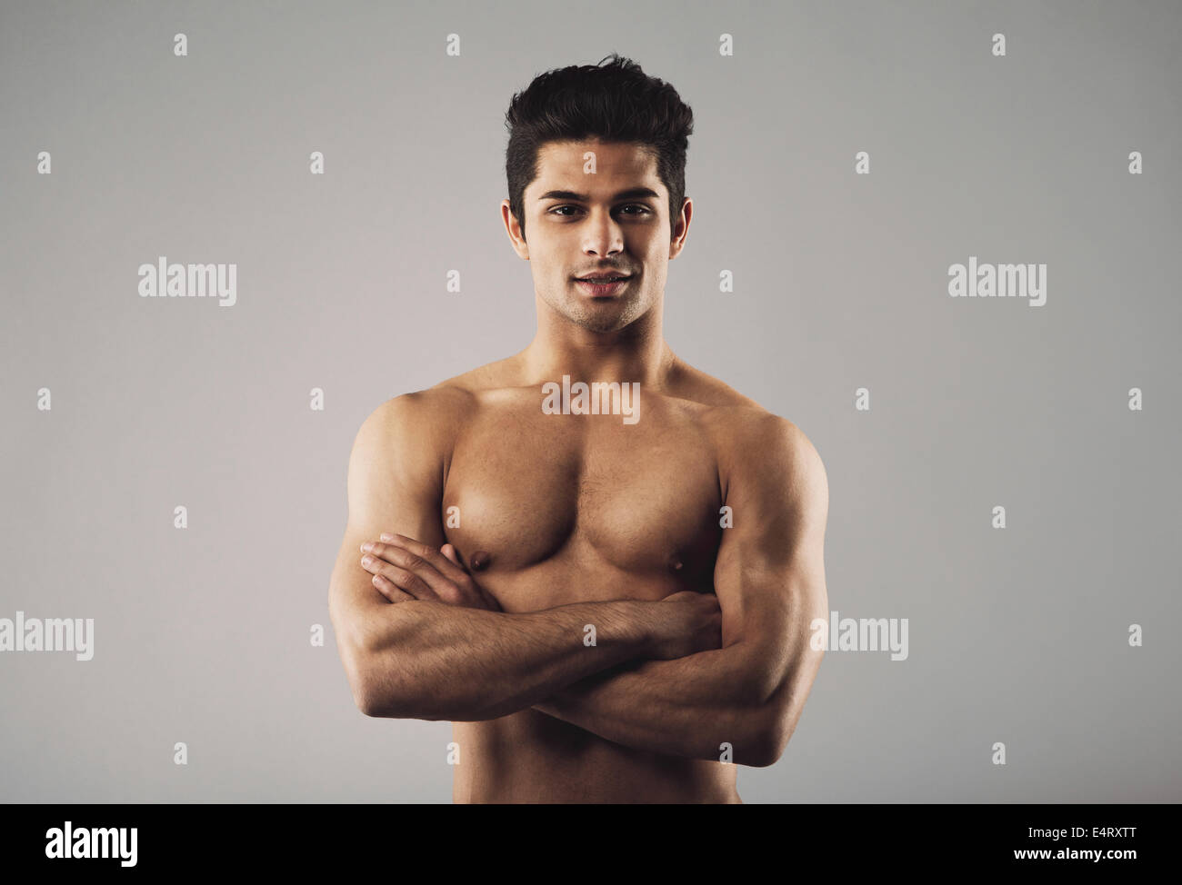 Portrait of a bare-chested muscular man standing with his arms crossed. Fit and masculine young hispanic man shirtless - Stock Image
