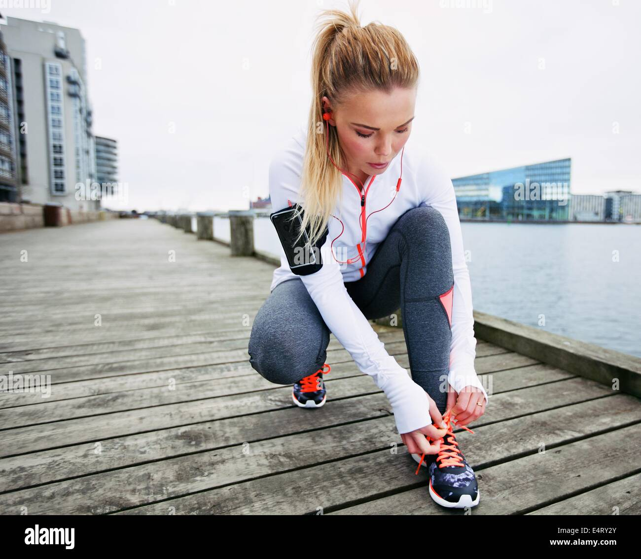Fit and sporty young woman tying her laces before a run. Female runner tying her shoelaces while training outdoor. - Stock Image