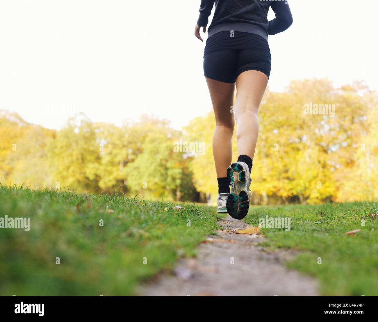 Rear view of woman athlete jogging in park. Female fitness model running outdoors - Stock Image