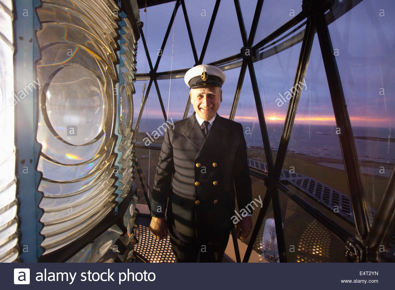 The lighthouse keeper stands by the lens of the North Ronaldsay Lighthouse, North Ronaldsay, Orkney, Scotland. - Stock Image