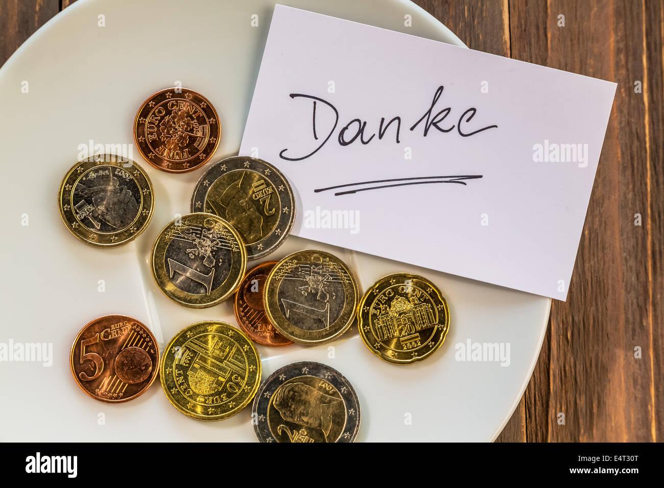 Plate with coins - tip, Teller mit Muenzen - Trinkgeld - Stock Image