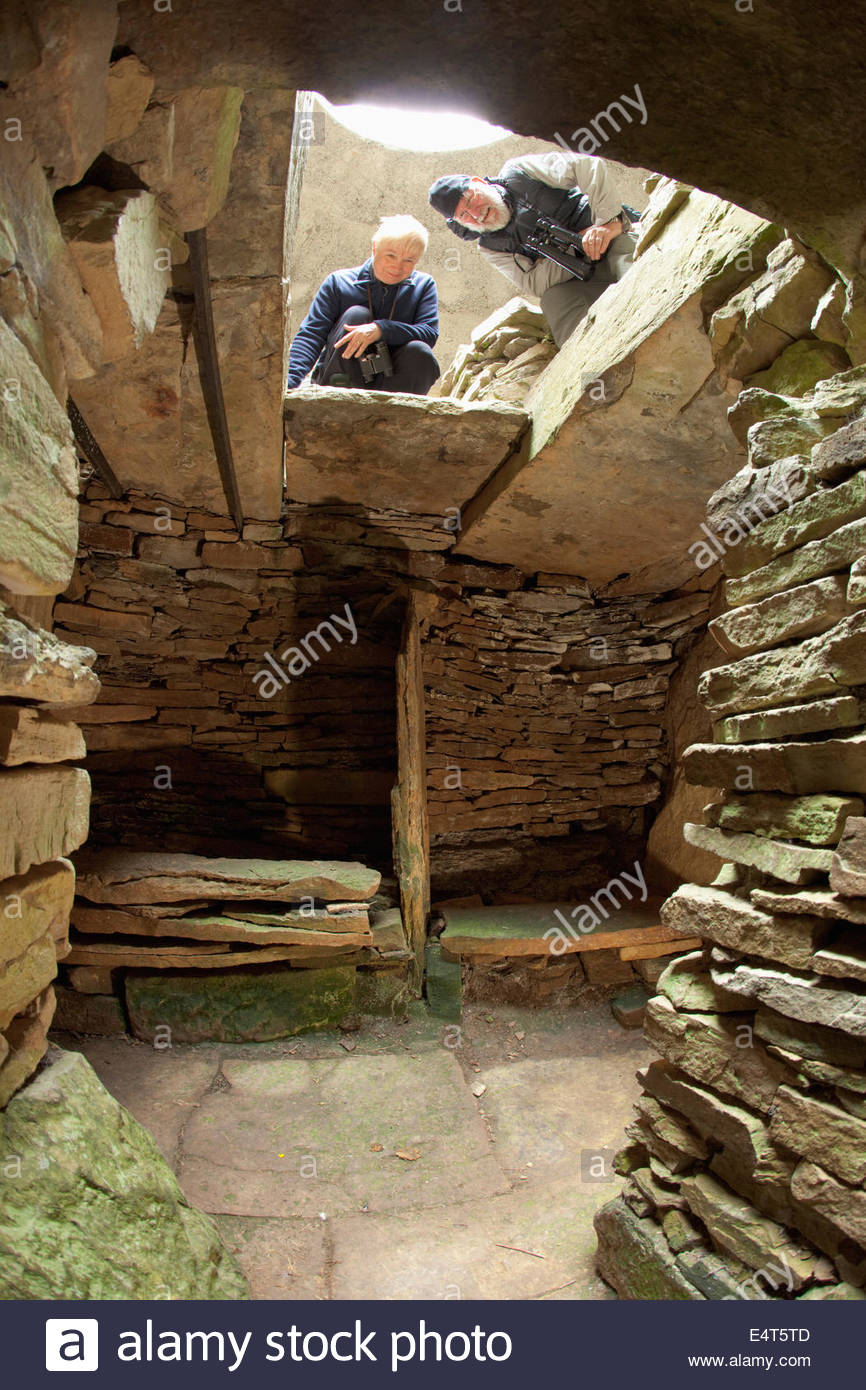 Visitors at the Taversoe Tuick Chambered Cairn on the Isle of Rousay, Orkney, Scotland. - Stock Image