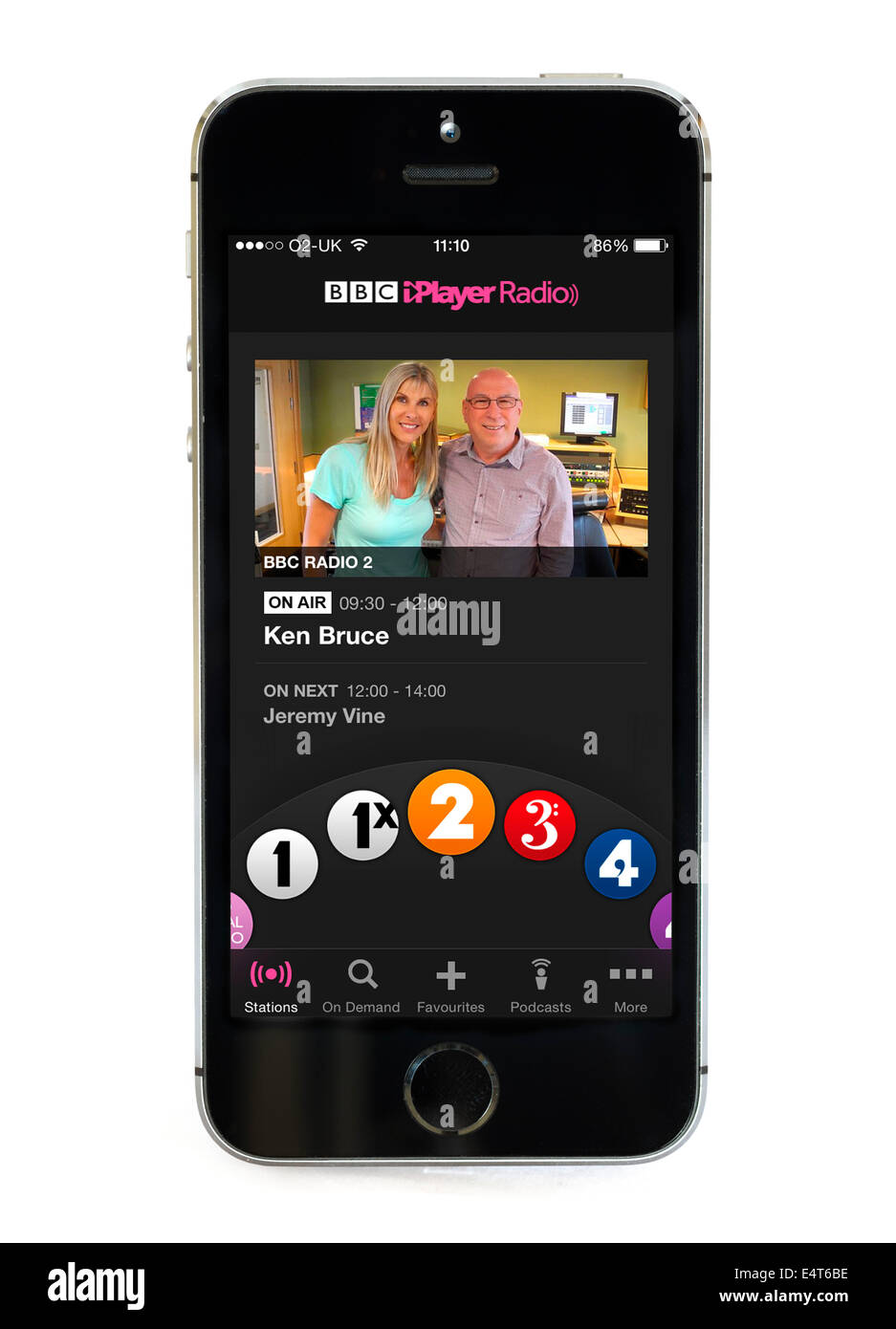 Listening to the Ken Bruce show via the BBC iPlayer Radio app on an Apple iPhone 5S, UK - Stock Image