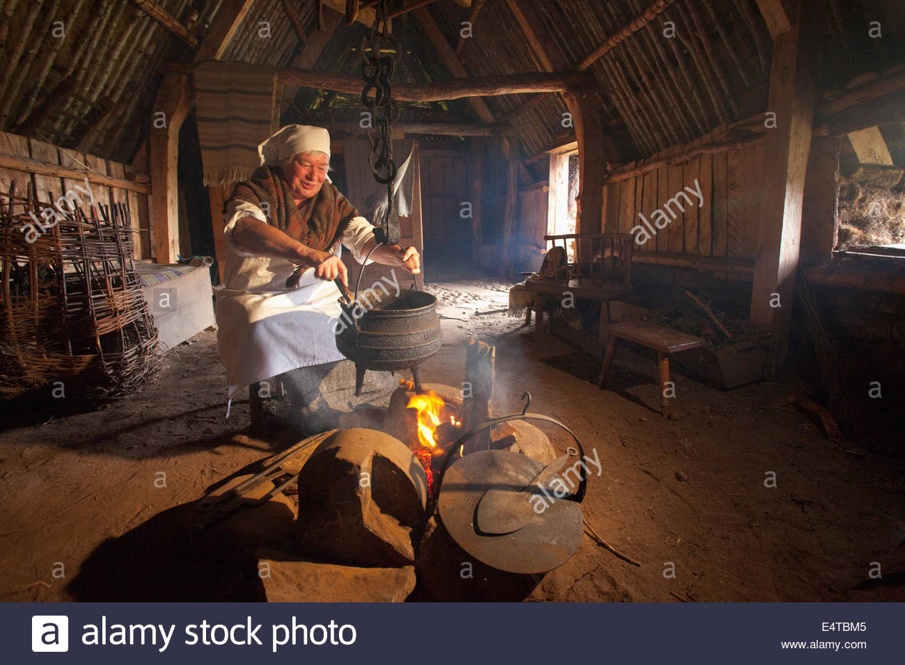 A woman in traditional costume cooking in the traditional way at the Highland Folk Museum, Newtonmore, Highlands - Stock Image