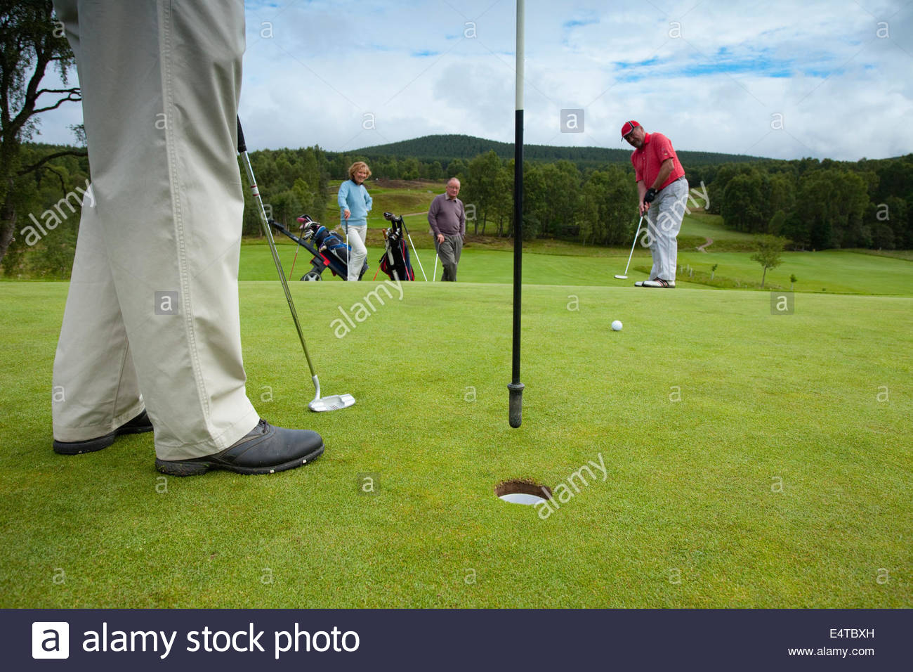 Four people play a round of golf at the Carrbridge Golf Club, Cairngorms National Park, Highlands of Scotland. - Stock Image