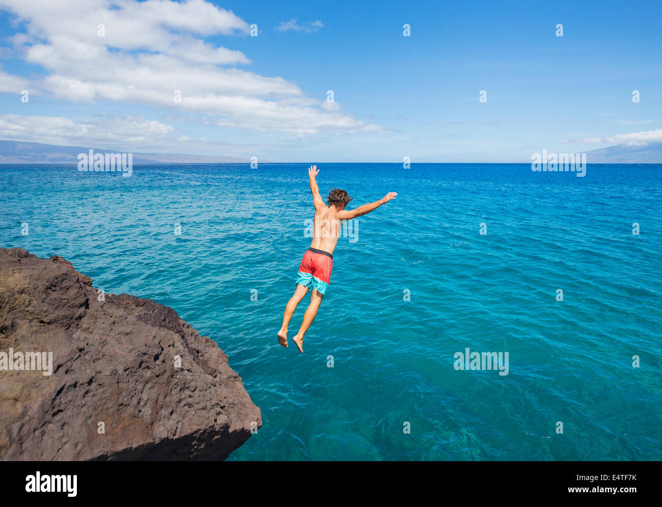 Man jumping off cliff into the ocean. Summer fun lifestyle. - Stock Image