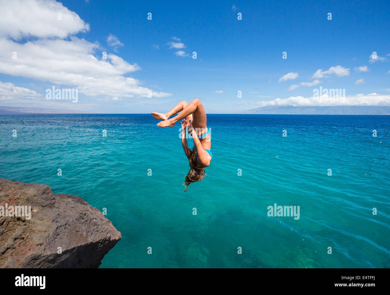 Woman doing backflip off cliff into the ocean. Summer fun lifestyle. - Stock Image