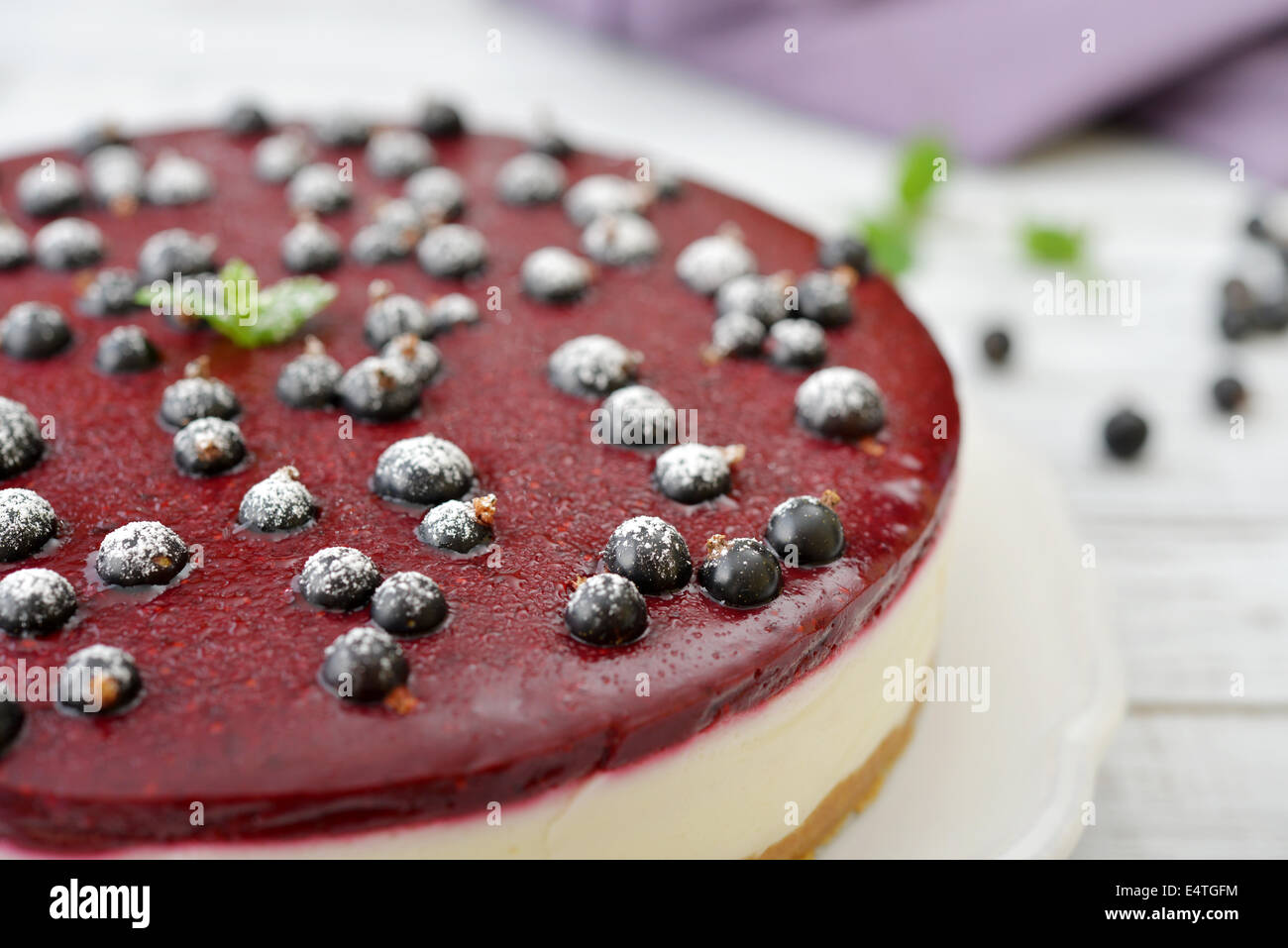 Black currant cheesecake with fresh berries on plate closeup - Stock Image