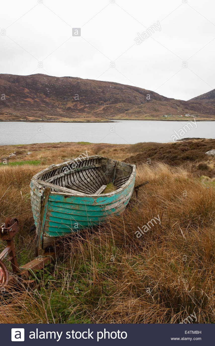 An old wooden boat abandoned by the side of a loch near Lochboisdale, South Uist, Outer Hebrides, Scotland. - Stock Image