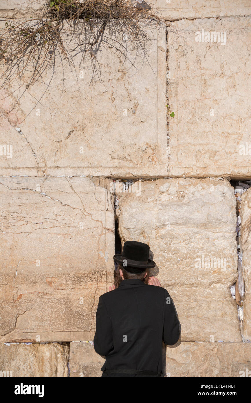 Jewish man prays next to a crack filled with letters containing written prayers at the Western Wall in Jerusalem. Stock Photo