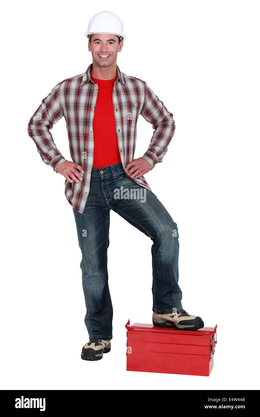 Male builder stood on toolbox - Stock Image
