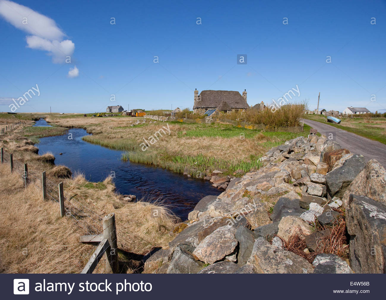 Thatched croft by a single track road at Howmore, South Uist, Outer Hebrides, Scotland. - Stock Image