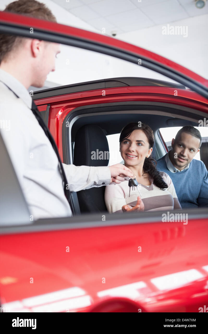 Smiling customer receiving car keys - Stock Image
