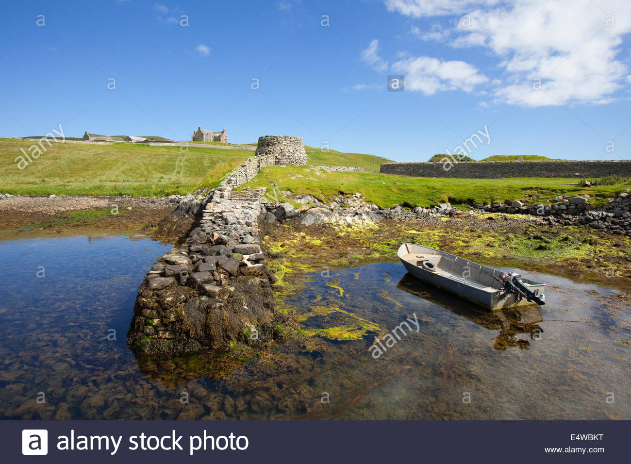 The old jetty at West Lunna Voe with the remains of a limekiln near Lunna House (visible beyond), Mainland, Shetland, - Stock Image