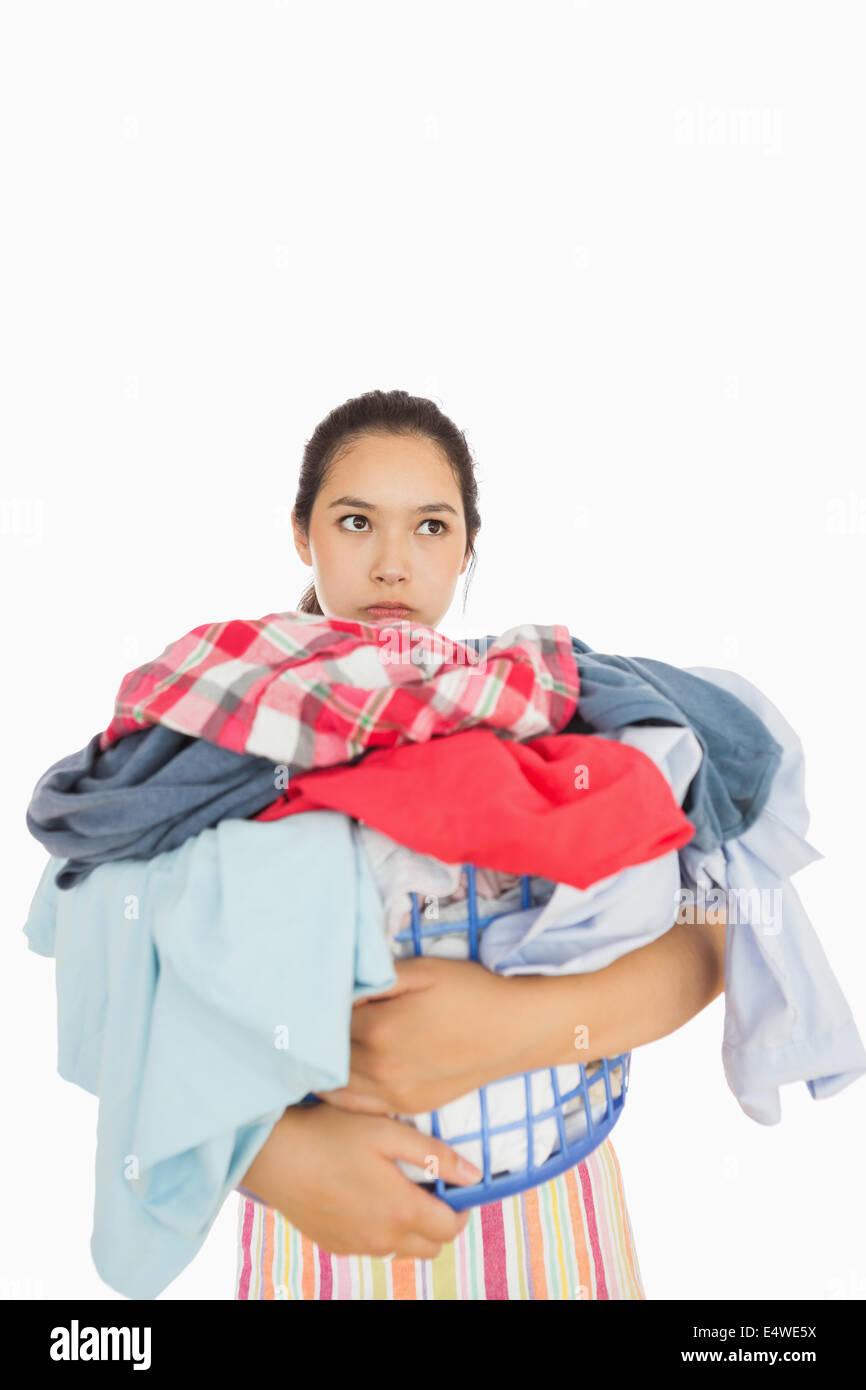 Exasperated woman holding laundry basket - Stock Image