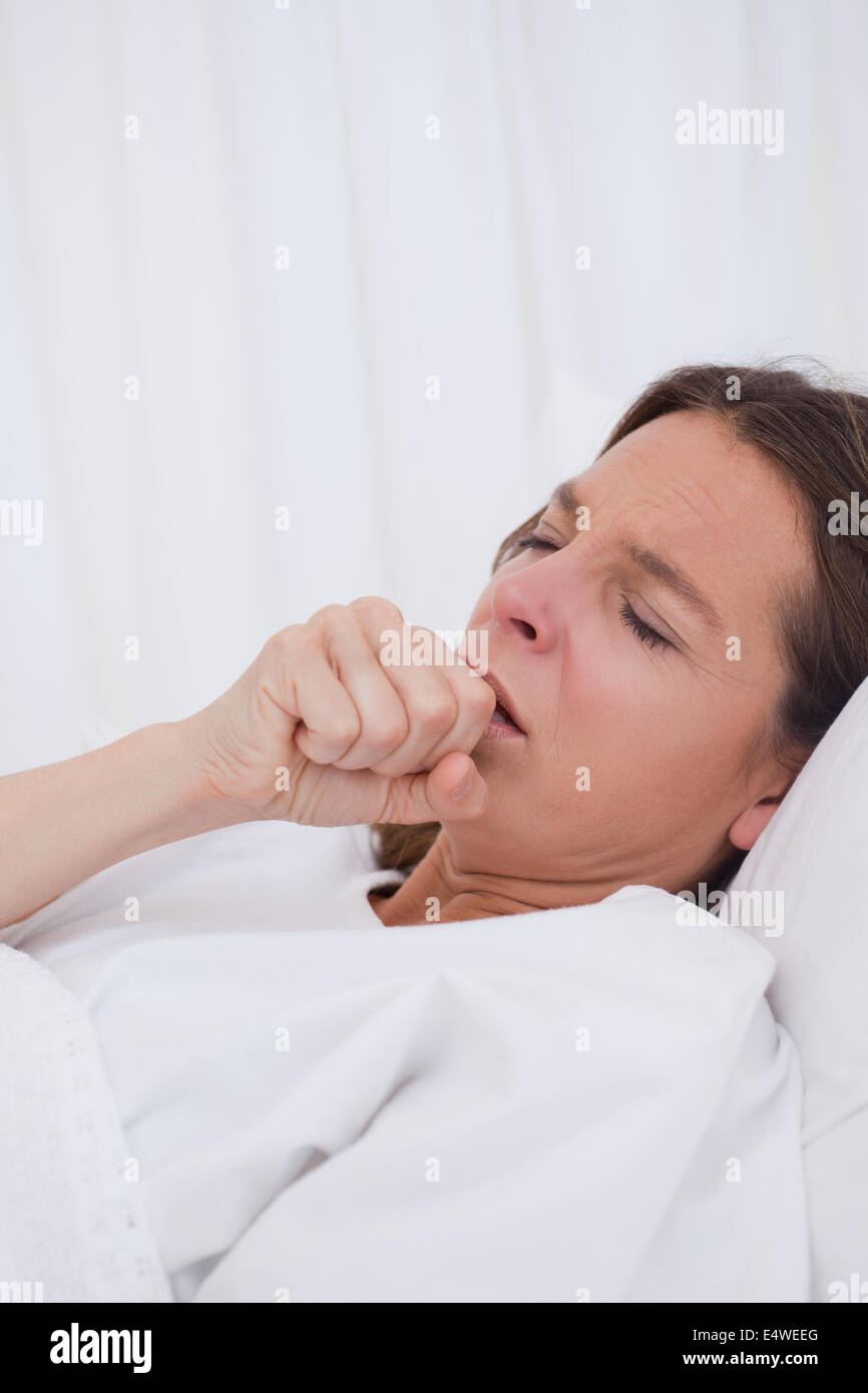 Woman in bed couching - Stock Image