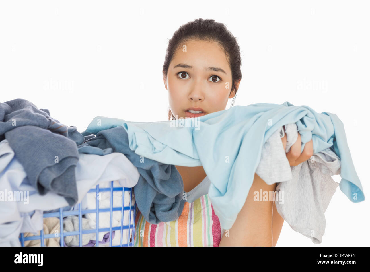 Frowning woman taking out dirty laundry - Stock Image