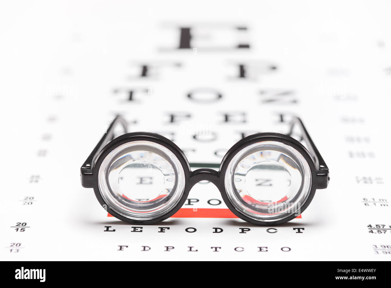 Studio shot of a pair of nerdy glasses on an eye chart with the focus on the glasses isolated on white background - Stock Image