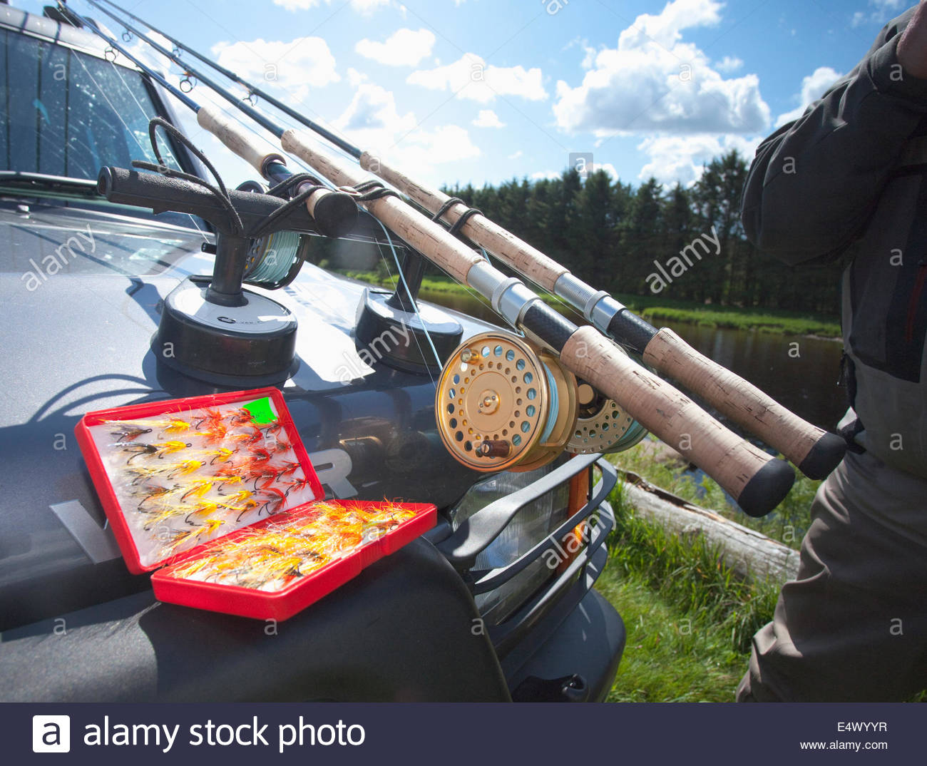 A selection of fishing flies and rods on the bonnet of a car, Scotland - Stock Image