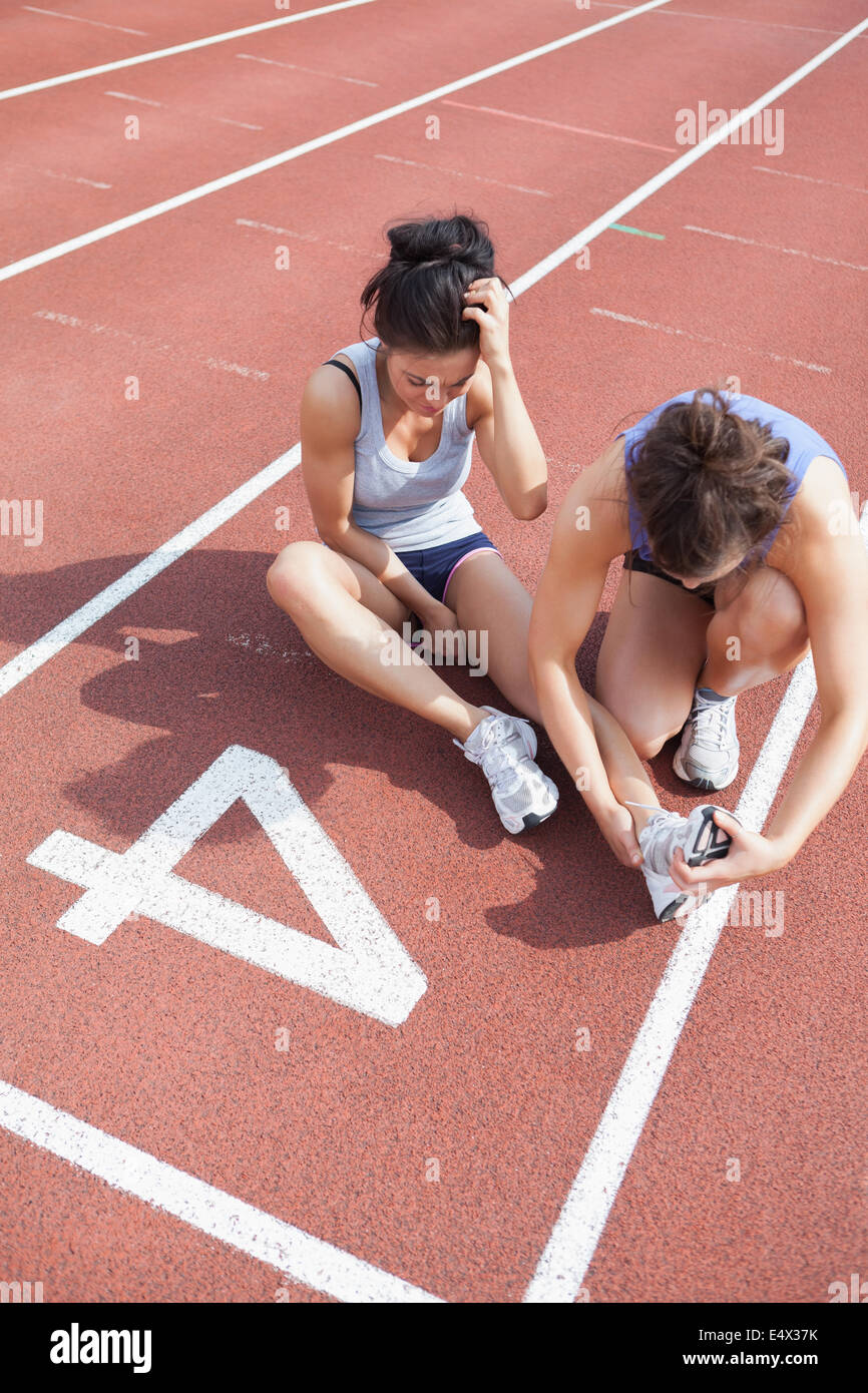 Woman caring about runner with sports injury Stock Photo