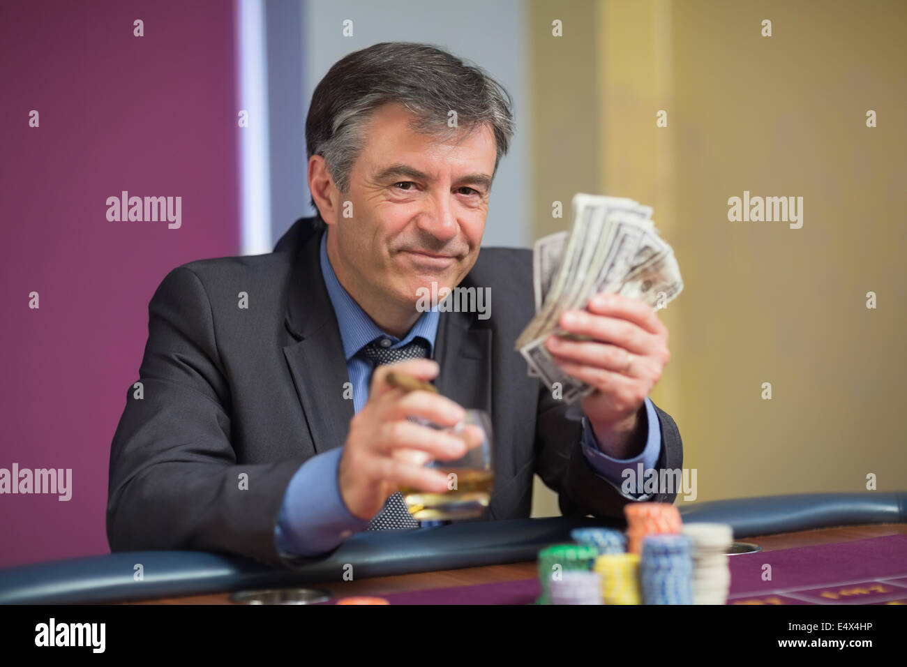 Man holding money smiling at roulette table - Stock Image
