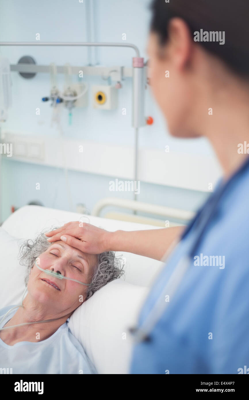 Patient lying on a bed closes her eyes - Stock Image