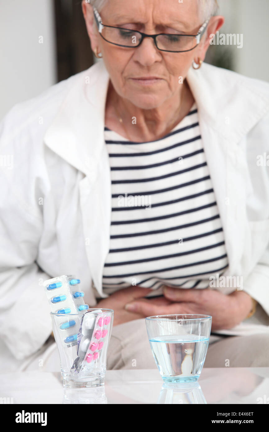 Woman about to take pain relievers - Stock Image